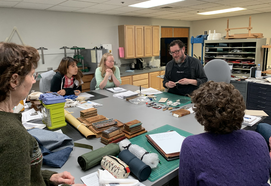 Jeff Peachey leading a discussion on conservation of leather bindings around a lab table in the Conservation Lab at the University of Notre Dame.
