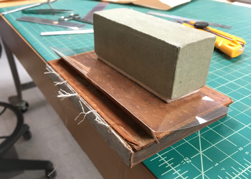Book with the boards placed in position for reattaching.