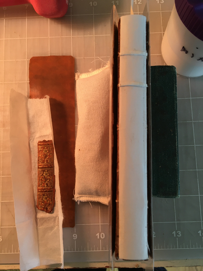 The book with the finished hollow tube and false bands attached. Next to the book is the piece of new lether and the fragment of the original spine piece.