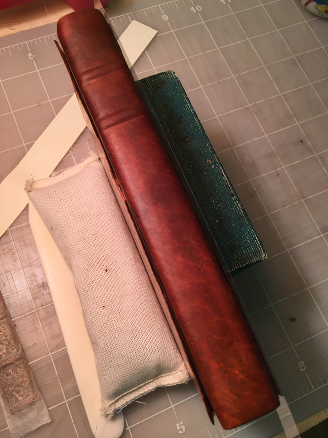 The new leather has beene pasted onto the book and is darkened from all the moisture.