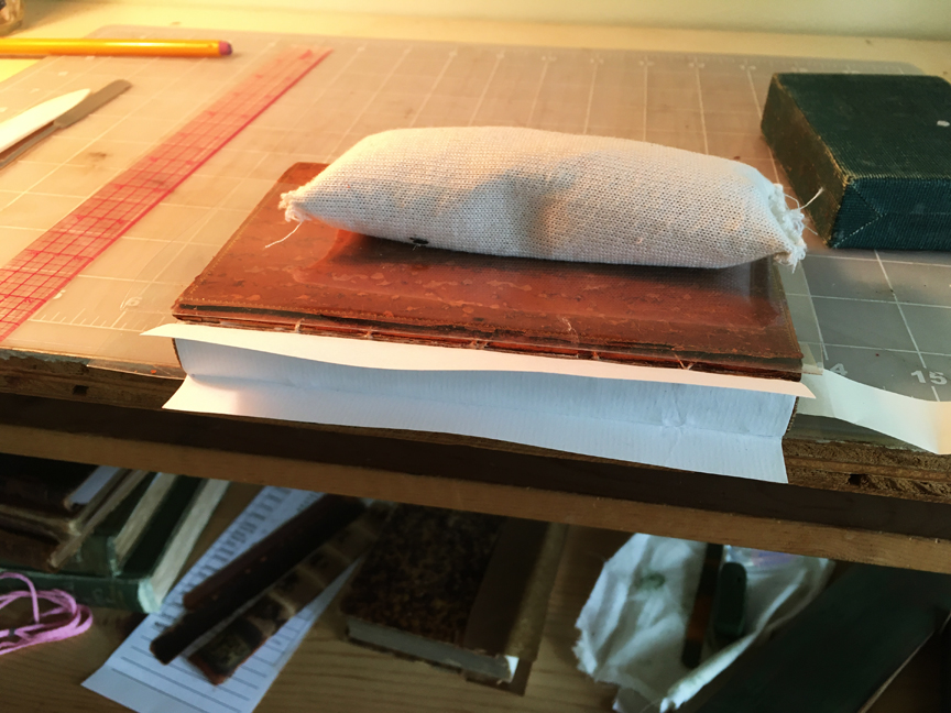 View of the spine area of the book with a piece of paper glued to it, the first step to forming a holow tube.