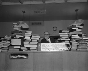 Books piled high on the library circulation desk with a man resting his heand in his hand.