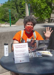 Greg Eismin, Circulation Supervisor in Wells Library, waves while sitting at a table outdoors reading the New Yorker magazine and wearing a face mask.