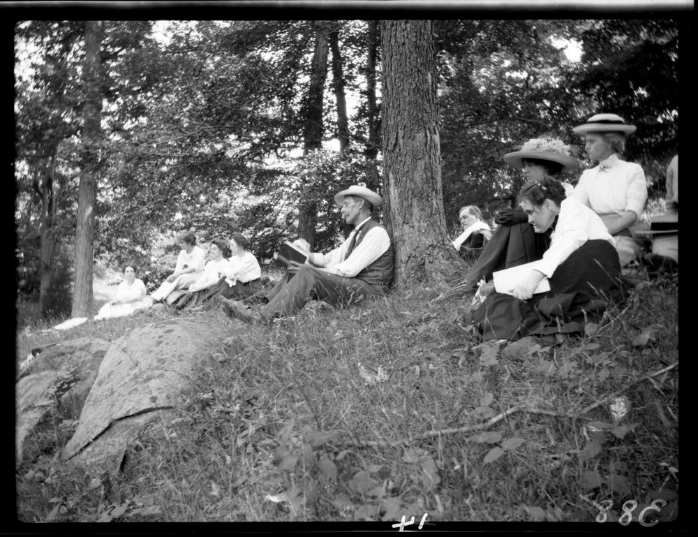 A group of people sitting in the woods reading books.