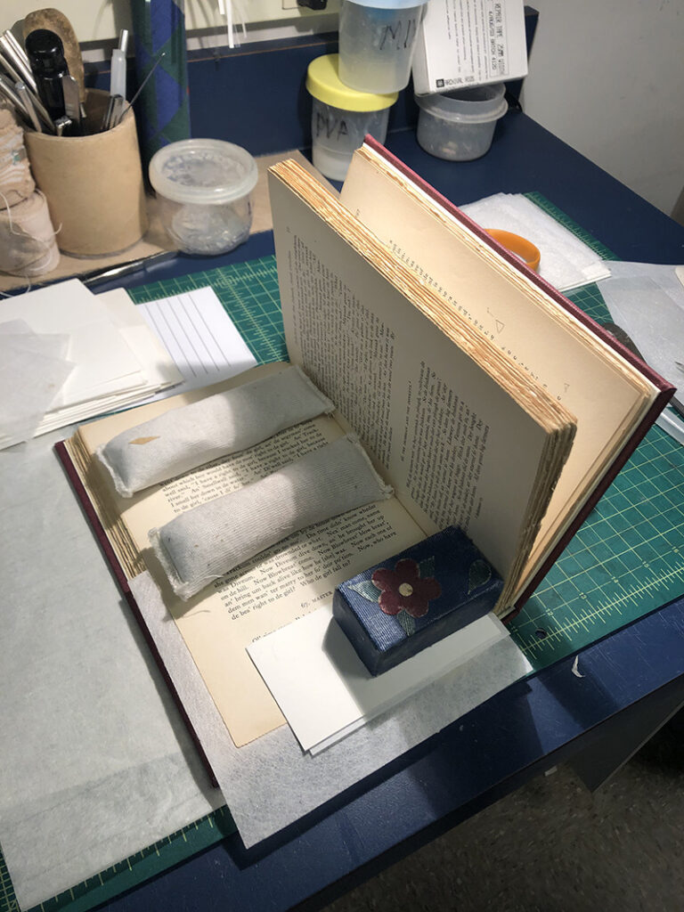 An open book with weights to hold it open while mended areas are drying.
