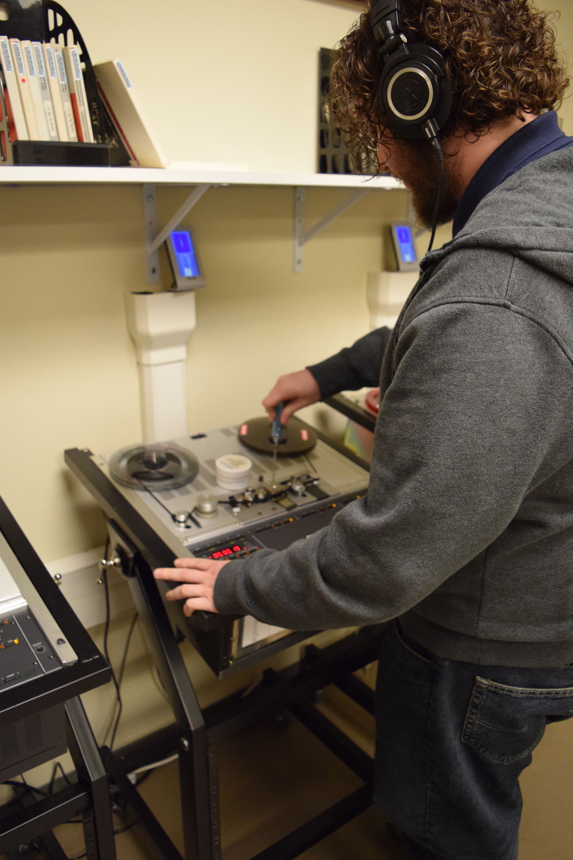 Digitization Technician making adjustments to audio tape decks.