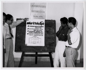 Students from the National Institute of Administration in Djakarta, Indonesia surrounding a flip chart listing goals for improving public administration practices.