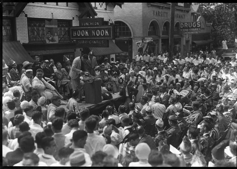 Crowd in front of the Book Nook, owner/manager Peter Costas standing at podium. Herman Wells seated to the left.