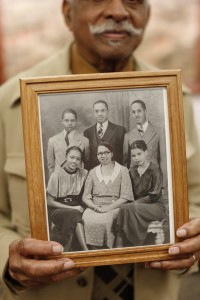 "Leon ""Parker"" Taylor holds the only photograph his family could locate of his mother, seated bottom middle surrounded by her children.  Parker is the young gentleman in the upper left corner. Photo courtesy Eric Rudd, Indiana University."