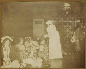 Women sitting on floor or standing, some dressed in men's clothing.