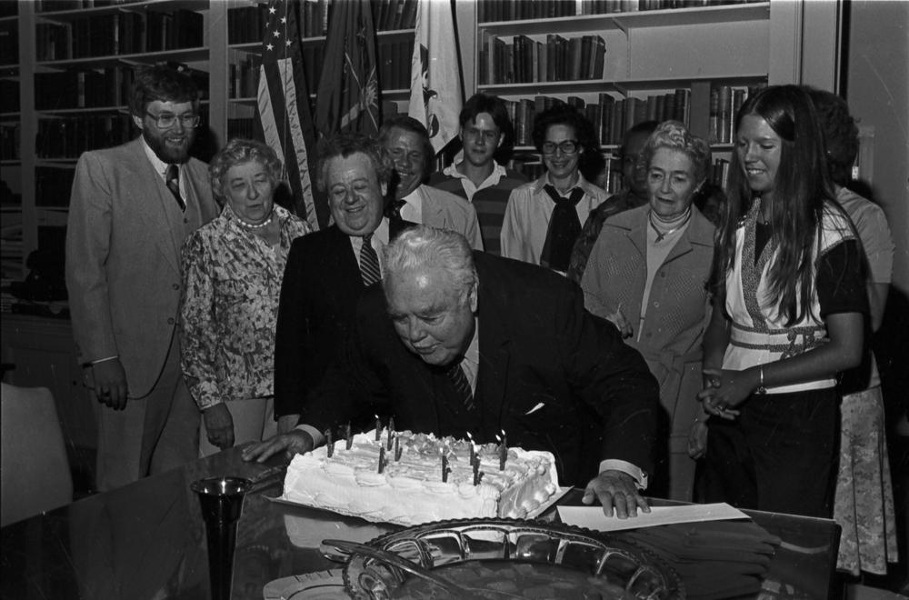 An older Herman B Wells blows out candles on his birthday cake in front of friends and staff
