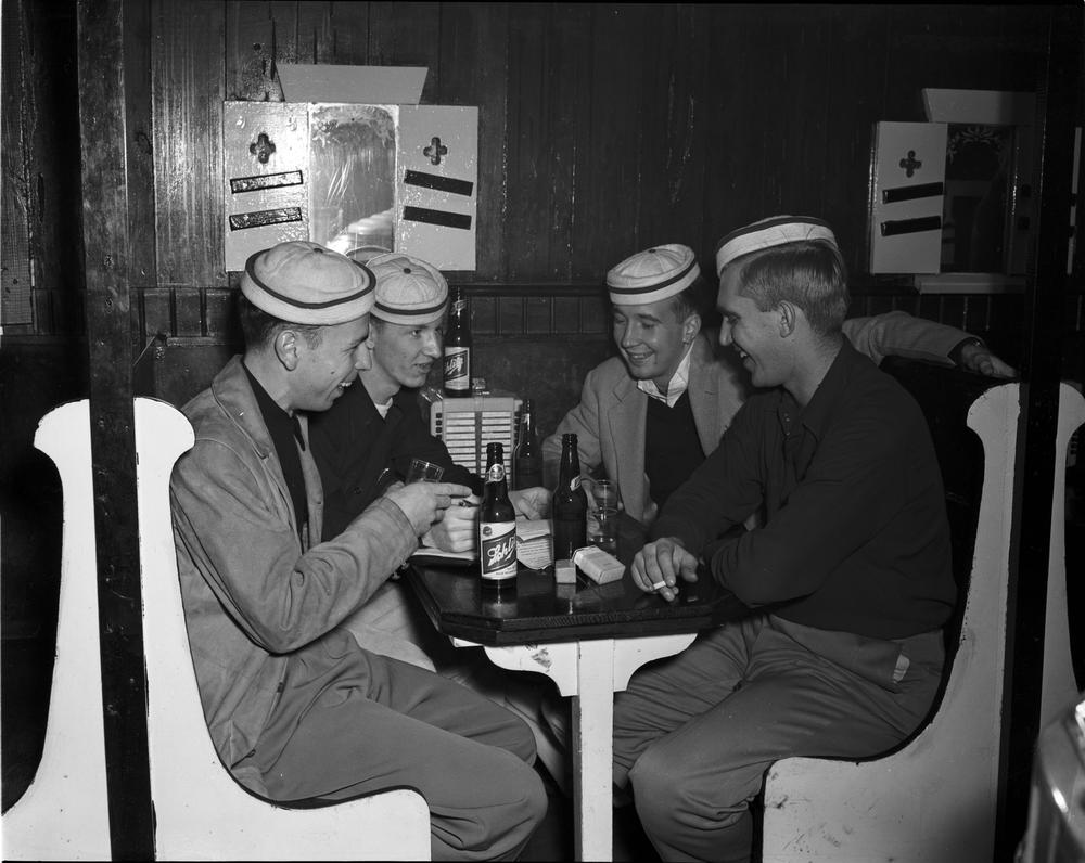 Officers of The Flame Club enjoy drinks at Nick's English Hut, 1949