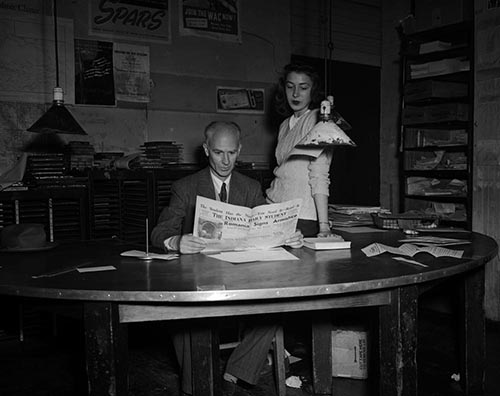 Black and white photograph of Ernie Pyle and Patricia Krieghbaum in the IDS office, November 1944