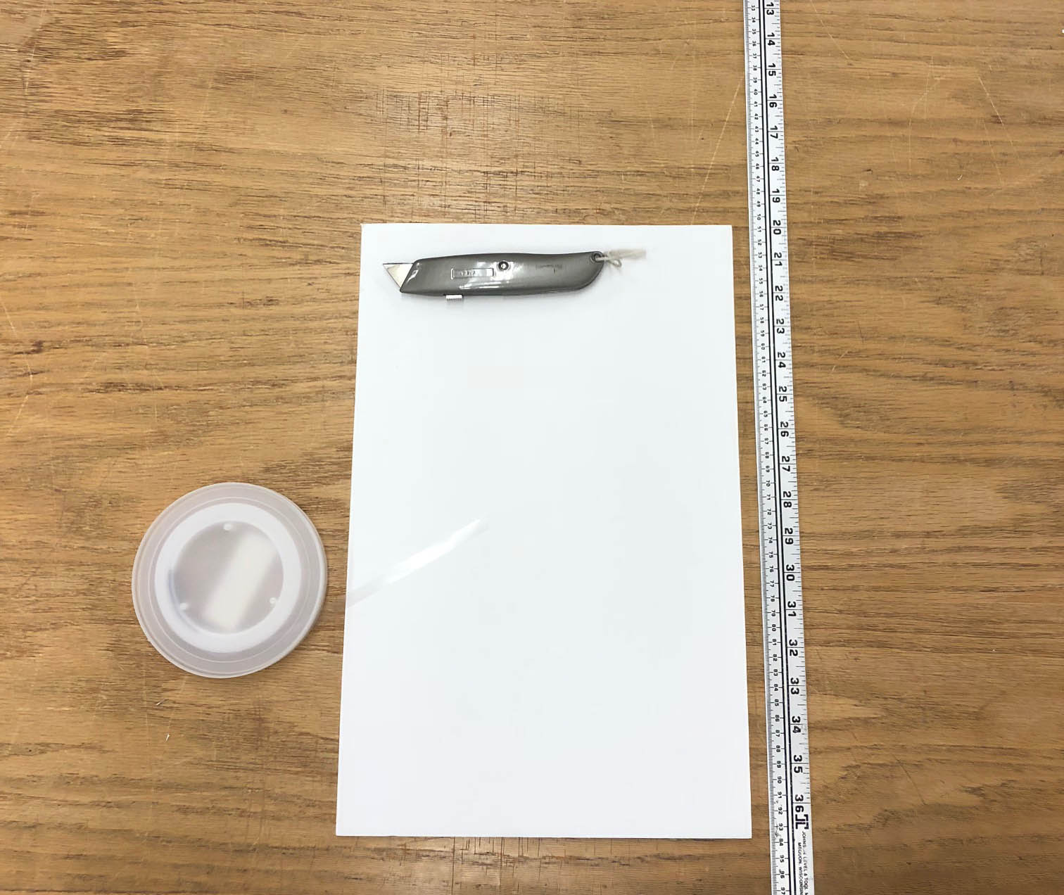 A roll of polyethylene book strapping, a piece of foam core, a utility knife, and a ruler on a table.