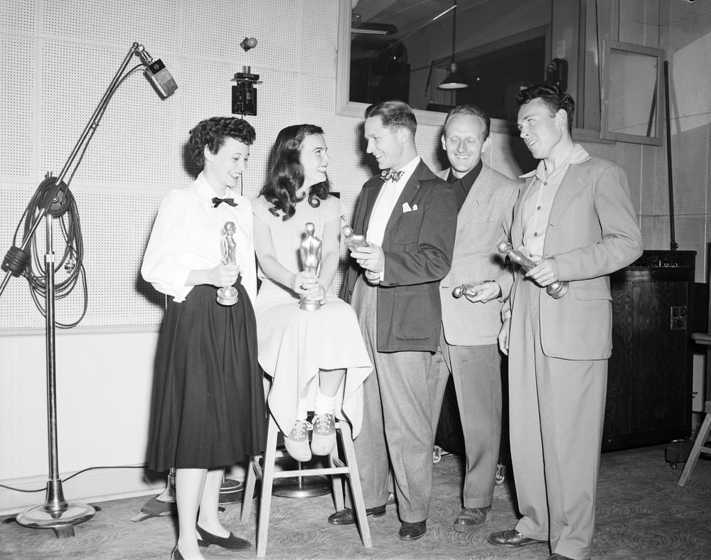 This is a black and white photograph of a group of 5 individuals who are each holding their Oscar award. Three men wearing suits stand to the right, while 2 women one standing and the other seated on a stool are to the left.