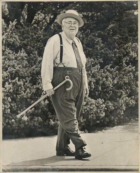 Herman B Wells walking with a cane in his right hand.