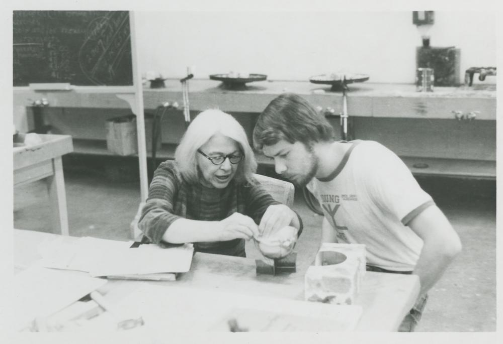 Black and white photograph of Alma Eikerman and a student seated side-by-side at a work table. Eikerman is demonstrating a technique for the student.