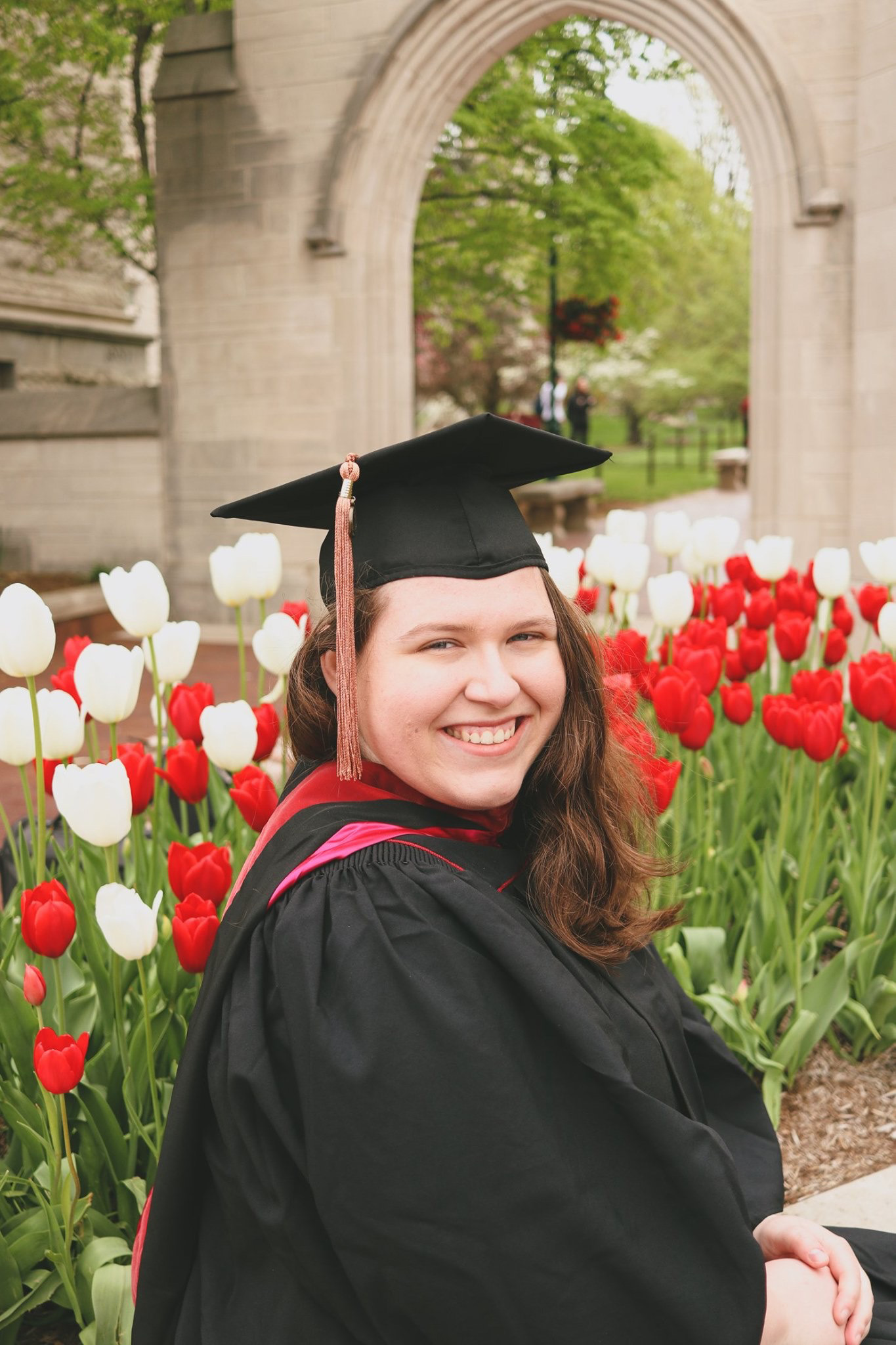 This is a color photograph of a student in a graduation cap and gown. She is seated in the front of the archway of the IU Sample Gates and is surrounded by red and white tulips.