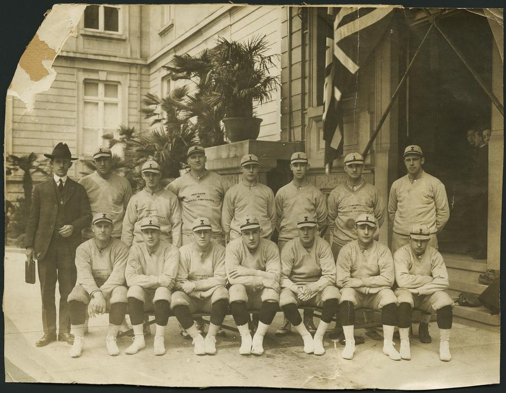 Black and white photograph of 14 members of the IU baseball team and their coach in front of their hotel