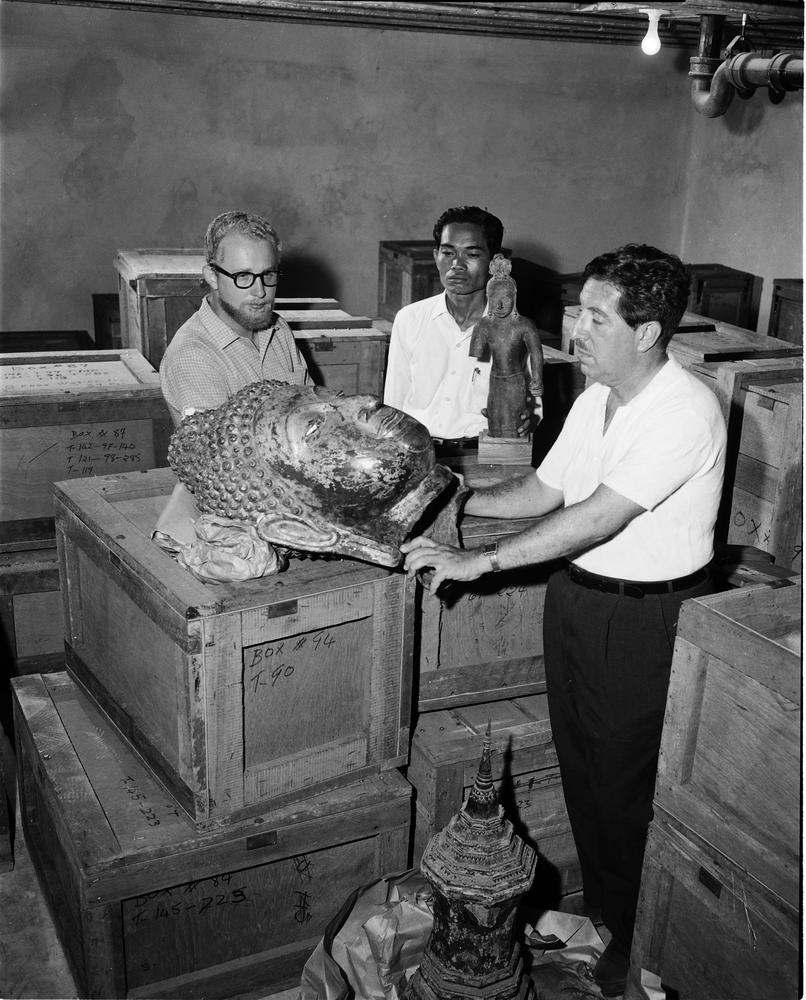 Black and white photograph of three men unpacking artwork of the Thai exhibition. They are surrounded by wooded crates, and two sculptures of the Buddha are visible.