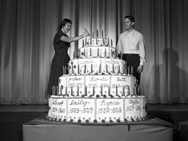 Black and white photograph of 2 students standing beside a large 5-tier cake with tapered candles.