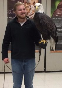 Color photograph of Will Schaust with a bald eagle perched on his arm.