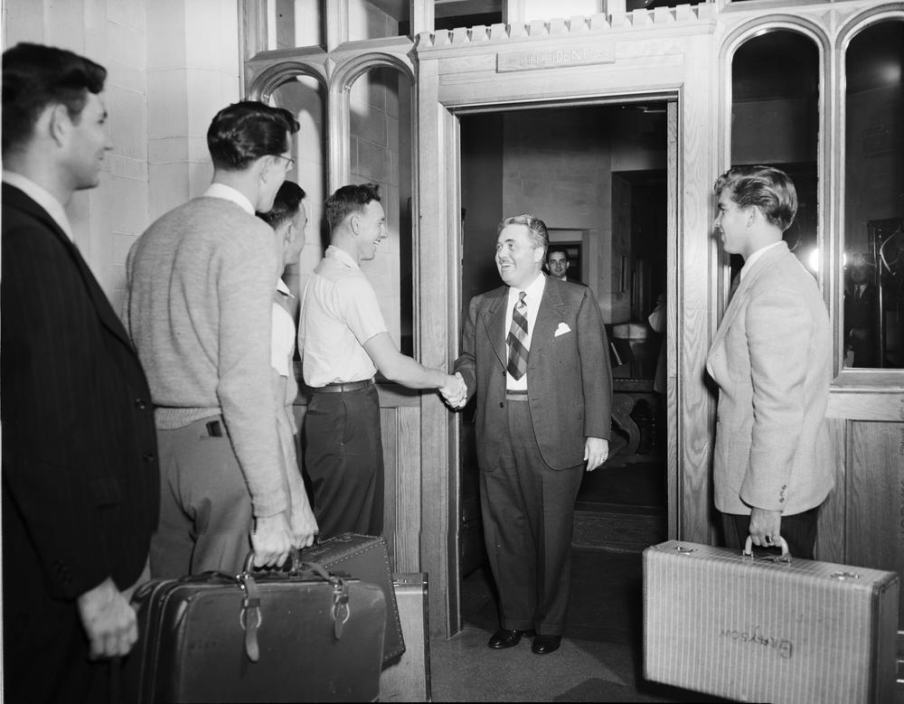 Black and white photograph of President Herman Wells greeting students with suitcases in hand at the entrance to Bryan Hall.