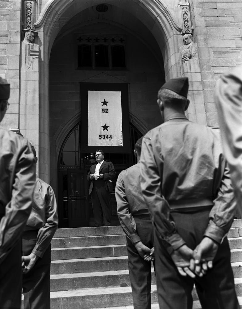 Black and white photograph of President Herman B Wells standing underneath the Service Flag. Uniformed male students stand in the foreground listening.