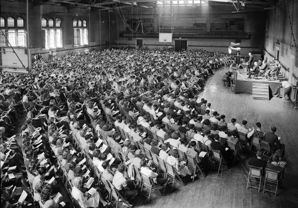 Black and white photograph of Freshman convocation - a large crowd of seated students surrounds a central stage.