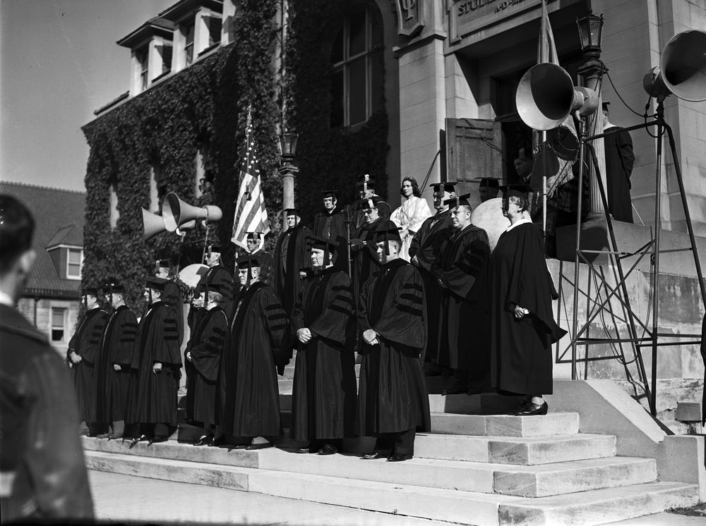 Black and white photograph of the Freshman Induction ceremony. Robed faculty and staff including President Wells stand on the front steps of the Student Building.