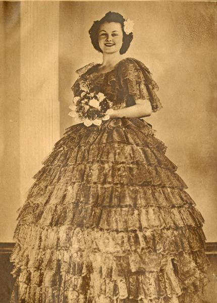 Black and white photograph shows Barbara VanFleit wearing a lace, tiered ballgown and holding a bouquet of flowers.