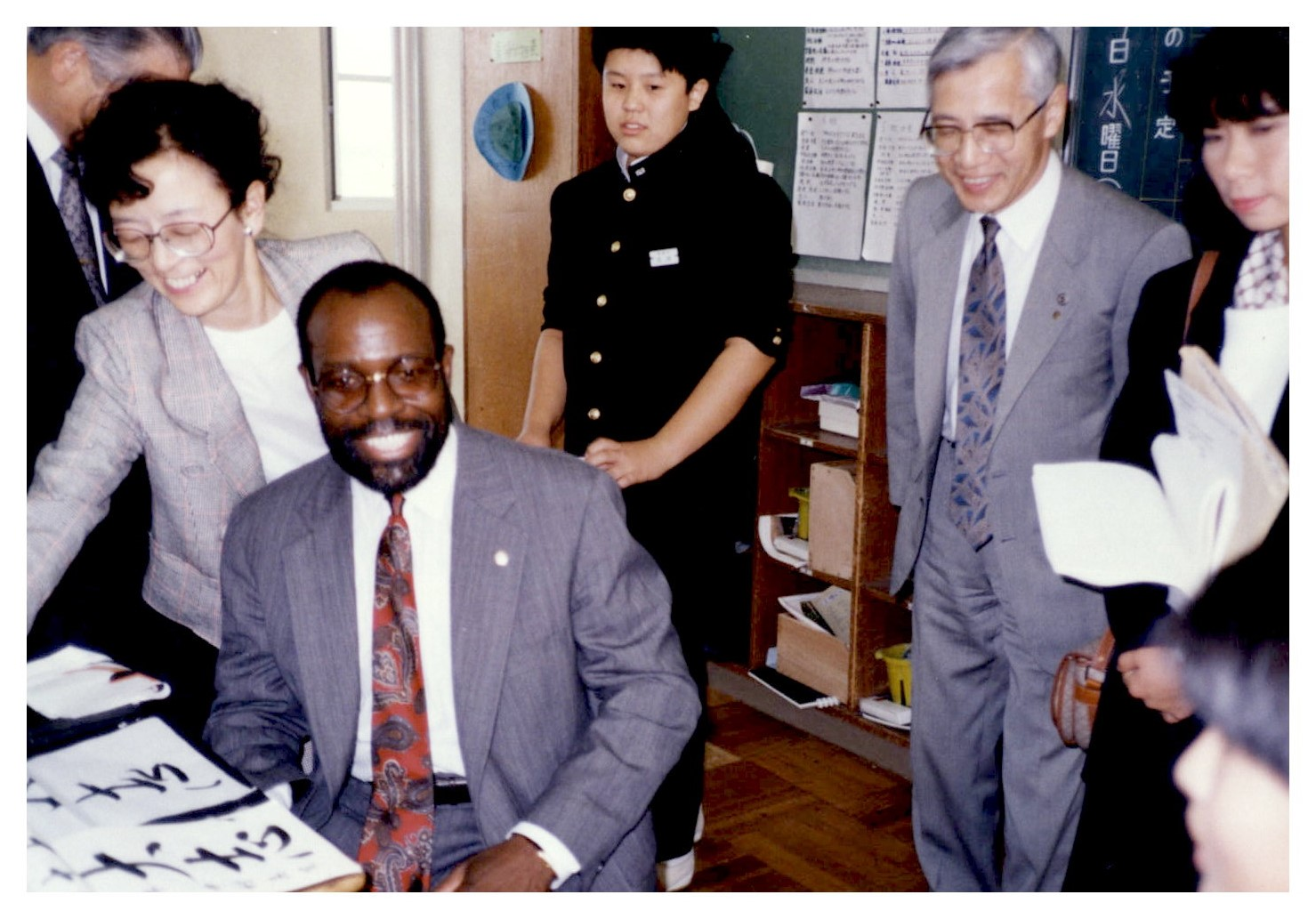 Charlie Nelms sits at a desk. Two women and two men stand nearby. On the desk are pieces of paper with Japanese character calligraphy.