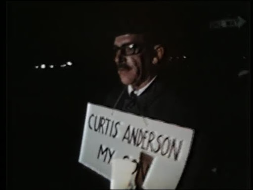 "Man walking with a sign around his neck that says ""Curtin Anderson, my son."""
