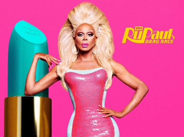 Picture of RuPaul next to a giant lipstick tube.