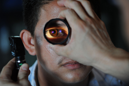 Image 1: Photo of man's eye being magnified, with another person's hand holding the magnifying tool