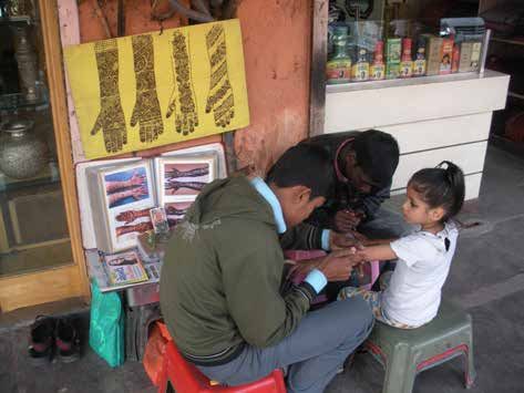Two male artists apply henna to a young girl in a marketplace.