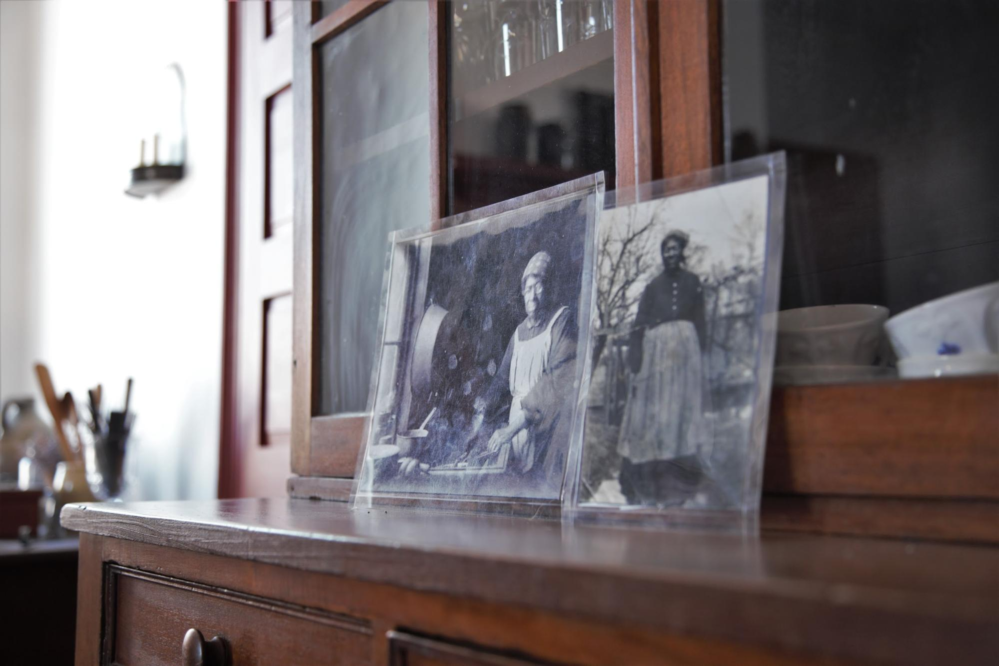 historic black and white pictures sitting on a china cabinet depicting African American woman